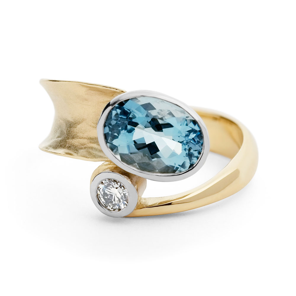 Anticlastic raised 18ct yellow gold ring with 18ct white gold settings, oval aquamarine and a diamond.